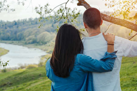 Couple of young beautiful man and woman hugging outdoors at sunny summer day at beautiful landscape background at countryside. Stock Photo