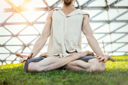 Close up of attractive athletic man practicing yoga and meditating in modern park at green grass outdoors. Stock Photo