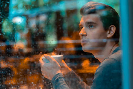 Young pensive handsome man drinking tea or coffee on rainy day and looking through the window.