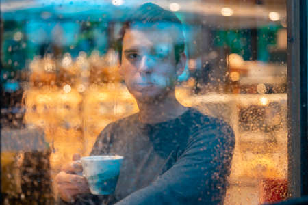 Young pensive handsome man drinking tea or coffee on rainy day and looking through the window. 版權商用圖片