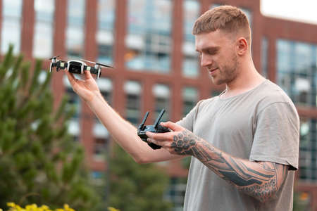 Young handsome man launching drone quadcopter at urban background. cityscape. modern device.