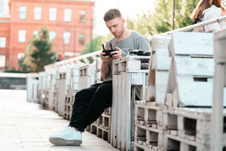 Young handsome man with drone quadcopter joystick controller at urban background. cityscape. modern device. Stock fotó
