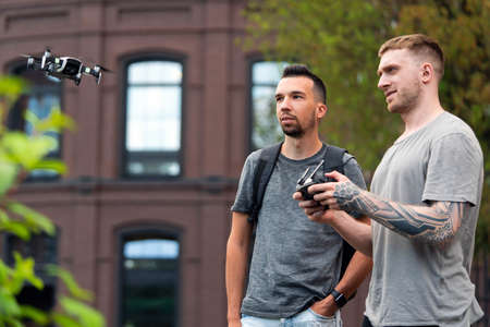Young handsome men launching drone quadcopter at urban background. cityscape. modern device.