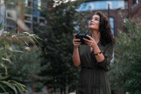 Young beautiful woman launching drone quadcopter at urban background. cityscape. modern device. Stock fotó