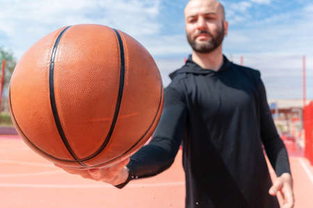 Close up of attractive man holding basket ball. Ball is on focus and foreground. Training outdoor