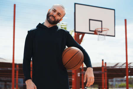 Attractive man on basketball court on basketball hoop and board background. Man is on focus and foreground, background is blurred. Stock fotó