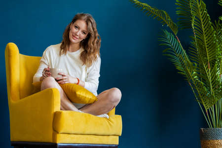 Young blonde woman reading book at home, drinking coffee or tea and sitting in yellow armchair. Cozy and comfortable timespending.