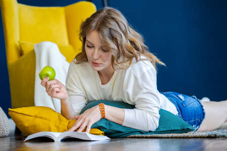 Young blonde woman reading book at home and laying on the floor with cushions next to yellow armchair. Girl eating green apple. Cozy and comfortable timespending.