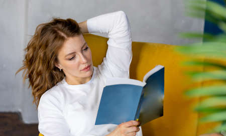 Young blonde woman reading book at home and sitting in yellow armchair. Cozy and comfortable timespending. Stock fotó