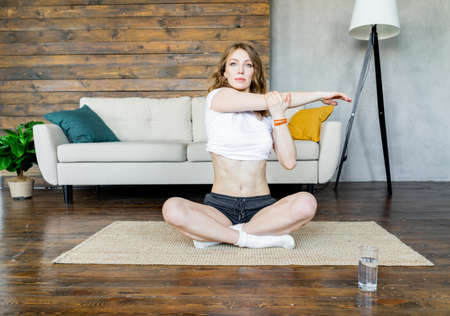 Young blonde woman doing stretching yoga exercises at home. Healthy lifestyle. Relaxation and wellbeing. Harmony with yourself.