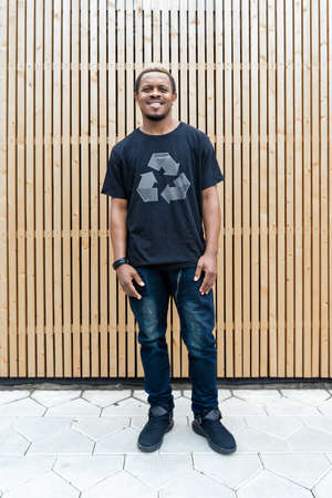 Young attractive man in black t-shirt with recycle symbol on wooden background. Eco symbol. Minimalism