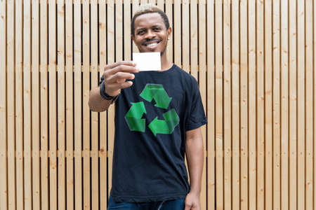 Young attractive man in t-shirt with recycle symbol on wooden background holding blank business card. Eco symbol. Stockfoto