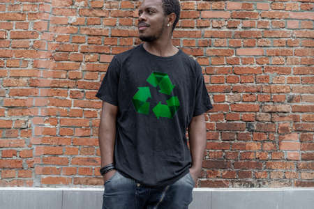 Young attractive man in black t-shirt with recycle symbol on brick background. Eco symbol. Minimalism