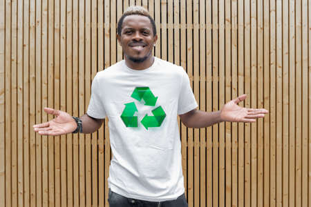 Young attractive man in white t-shirt with recycle symbol on wooden background. Eco symbol. Minimalism Stockfoto