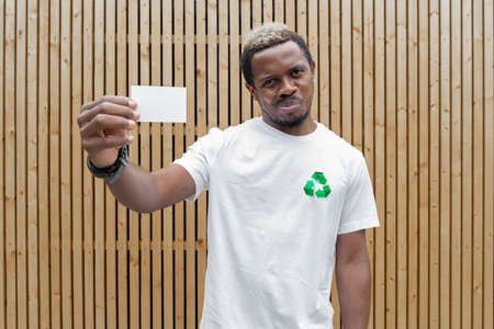 Young attractive man in t-shirt with recycle symbol on wooden background holding blank business card. Eco symbol. Minimalism Stockfoto