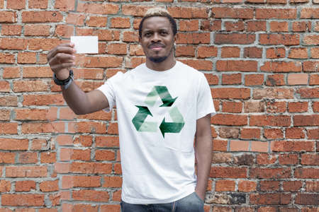 Young attractive man in t-shirt with recycle symbol on brick background holding blank business card. Eco symbol. Minimalism Stockfoto