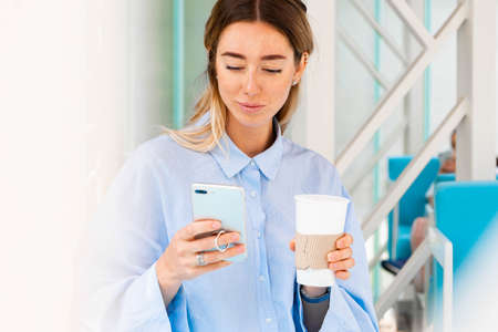 Young and attractive woman drinking coffee from coffee eco biodegradable cup at modern park and holding mobile phone. Eco friendly take away mug.