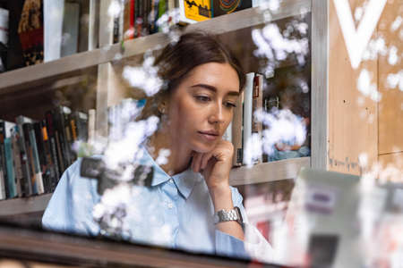 Young and pensive attractive woman working on laptop in modern library with big windows. Freelance concept. Young successful entrepreneur.