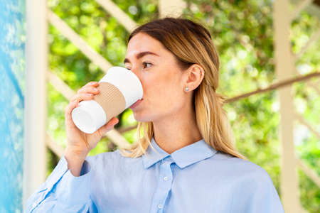 Young and attractive woman drinking coffee from coffee eco biodegradable cup at modern park. Eco friendly take away mug.