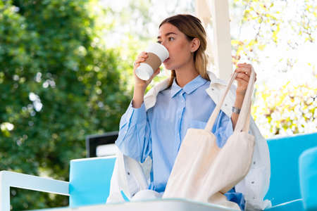 Young and attractive woman drinking coffee from coffee eco biodegradable cup at modern park and holding cotton blank white canvas bag. Eco friendly take away mug and bag. Reklamní fotografie