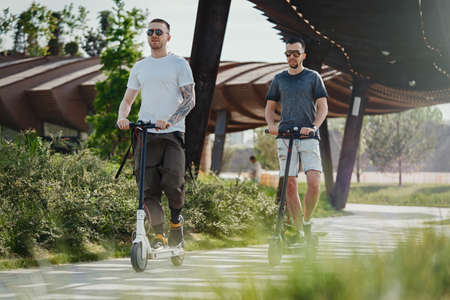 Two men riding white and black electric kick scooters at beautiful park landscape. Men is on foreground, modern building and park is on background. Stock fotó