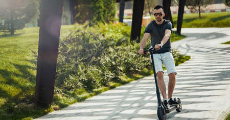 Attractive man riding electric kick scooter at beautiful park landscape. Man is on foreground, modern building and park is on background. Banco de Imagens
