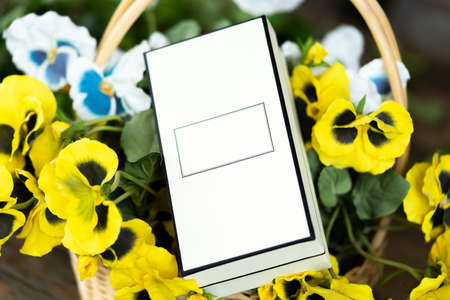 Close up of blank white box in basket with flowers on wooden table.