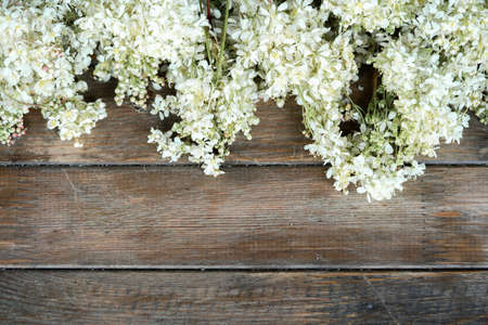 Close up of white flowers on wooden rustic table at countryside. Zdjęcie Seryjne - 128906671