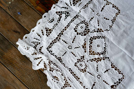 Close up of white rustic cotton table cloth on wooden table.