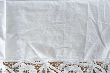 Close up of white rustic cotton table cloth on wooden table. Zdjęcie Seryjne - 128906670
