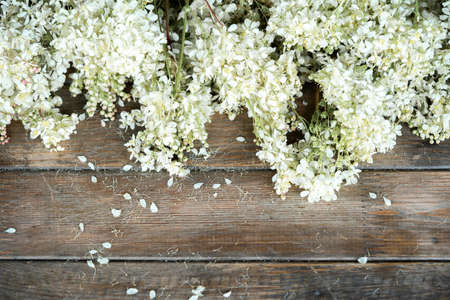 Close up of white flowers on wooden rustic table at countryside.