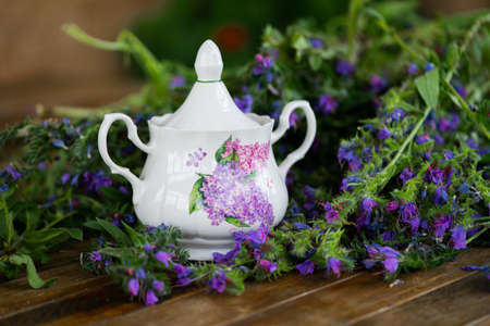 Close up of sugar bowl with violet petals and flowers on wooden Rustic table