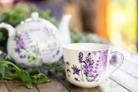 Close up of tea cup and teapot with violet petals and flowers on wooden Rustic table