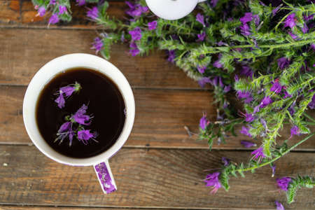 Close up of tea cup with violet petals and flowers on wooden table.