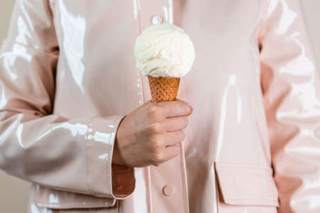 Close up of woman in pink raincoat holding vanilla ice cream in waffle cone. Minimalism concept.