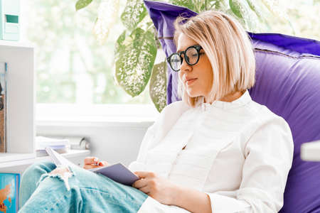 Young attractive smiling woman makes some notes in notepad at library and sitting on violet couch.