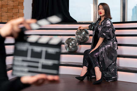 Blurred Clapper Board And Woman Actor On Stage. Movie Or Clip Production Backstage. Singer Super Star Near Discoballs Stock Photo
