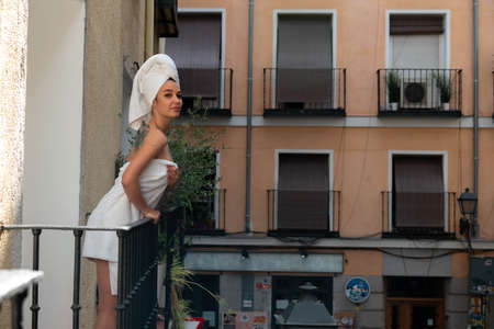 Beautiful Woman at Balcony in European Old Downtown Enjoying Weather And Sun After Taking Shower. Stay Home Concept. Strolling Without Leaving Home Zdjęcie Seryjne
