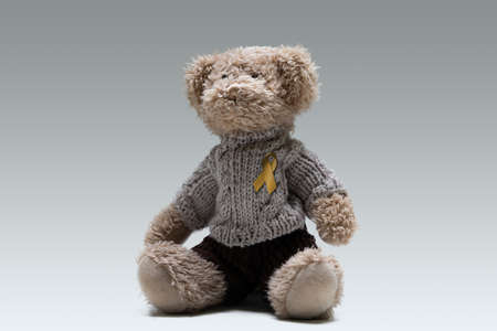 Teddy Bear With Golden Yellow Ribbon on Gray Background. Campaign Support Childhood Cancer Awareness
