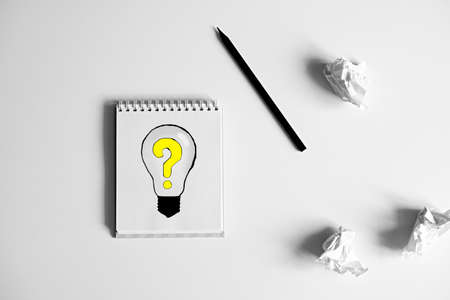 Pen And Crumpled Paper Near Notepad With Drawing Of Bulb With Question Mark on White Background. Artist, Author, Painter, Journalist, Inventor Waiting For Inspiration