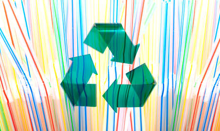 Green Stylish Recycle Arrow on Multicolored Plastic Straws Background. Reuse Sign. Environment Care Concept