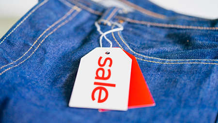 White Tag Price With Red Sale Inscription On Jeans. Discount and Promotion. Shopoholic and Consumerist. Sale Template Design