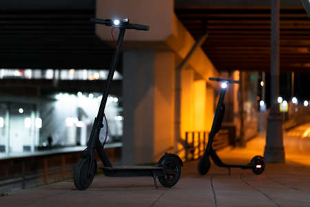 Close up of Black Electric Kick Scooters at Cityscape at Night Time. Kick Scooters Under Illuminated Bridge And Near Metro Station. Urban Transportation. Archivio Fotografico