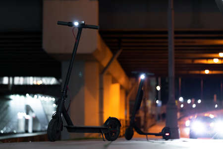 Close up of Black Electric Kick Scooters at Cityscape at Night Time. Kick Scooters Near Passing By Cars on Urban Background