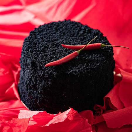 Creative Black Cake Decorated With Red Cayenne Pepper on Red Bright Background. Cake And Bake With Passion