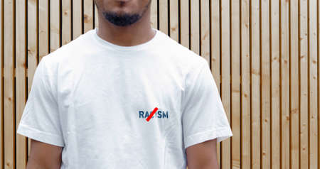 Dark Skinned Man In White T Shirt With No Racism Inscription. Tolerance and Social Equality. Archivio Fotografico