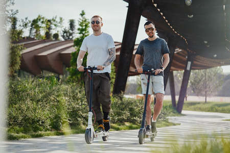 Two handsome men riding electric kick scooters at beautiful park landscape Archivio Fotografico