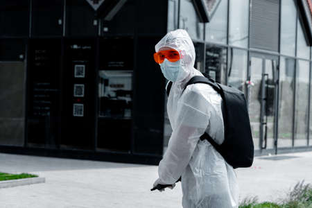Man Riding Electric Kick Scooter Near Modern Buildings and Wearing Anti COVID Protective Suit, Glasses, Medicine Mask and Gloves. 스톡 콘텐츠