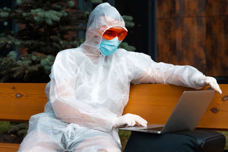 Young handsome Freelancer Man Wearing Anti COVID Protecting Suit, Mask and Glasses and Working On Laptop Outdoors.