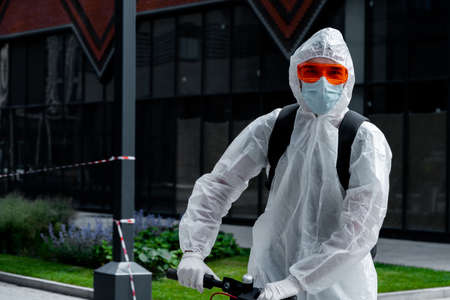 Man Riding Electric Kick Scooter Near Modern Buildings and Wearing Anti COVID Protective Suit, Glasses, Medicine Mask and Gloves. Urban Cityscape on Background.